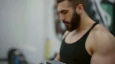 diluted : brutal muscular man with a beard drinks dilute amino acids from a shaker during training. restoration of destroyed muscle fibers