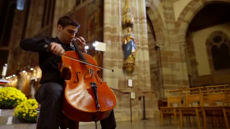 виолончель : Male cello player performing a song in a church, holy place.