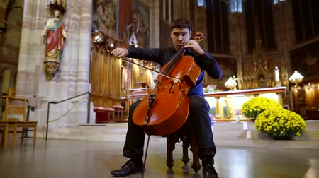 виолончель : Skilled male musician playing on a cello in a church hall.
