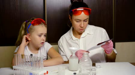 zvědavý : Mother and daughter conducting chemical experiment together, learning together.