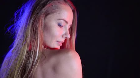 desire : Close-up shot of a passionate sensual blonde girl posing in studio against black background. Stock Footage