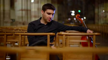 виолончель : Portrait of a handsome musician in black sitting in empty church with a musical instrument.