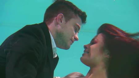 reunir : couple of newlyweds under water in wedding clothes hugging and kissing Vídeos