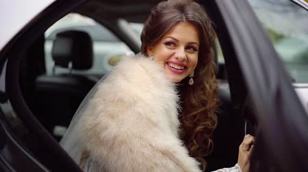 limuzína : pretty bride in a white dress looks out of the car of the wedding procession and smiles Dostupné videozáznamy