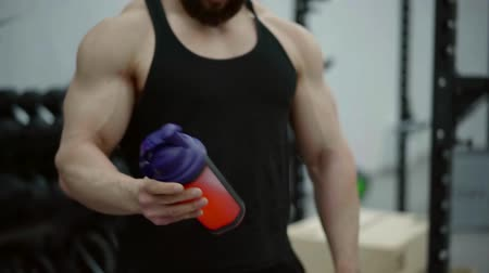 shaker : professional athlete stands in the gym in a black tank top and stirred in an amino acid shaker to restore damaged muscles
