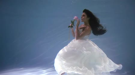 kept : general plan. cute bride in a wedding dress under water like in a fairy tale with an Orchid flower Stock Footage