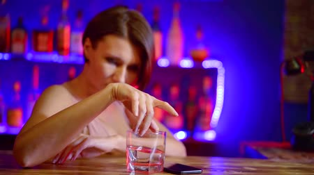 munkanélküliség : cute girl with short hair is sad in the evening at the bar with a glass of vodka and looks at the mobile phone screen