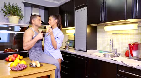 nyel : Happy couple chatting and having breakfast together at home in the kitchen Stock mozgókép