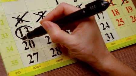 part of the frame : close up. woman hand marker on the calendar crosses off the past days of the week and plans activities for the remaining dates Stock Footage