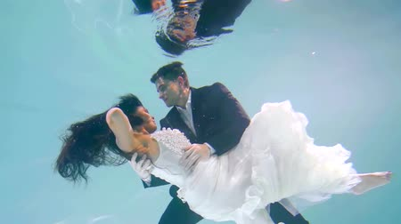 reunir : wedding under water. cute couple dancing in festive clothes in the pool like in a fairy tale. beautiful white dress Stock Footage