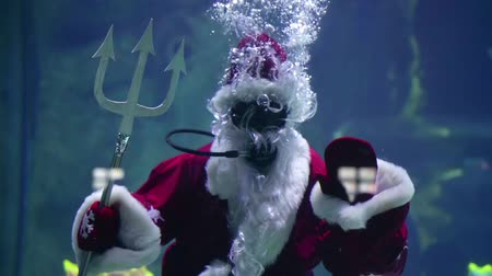üdvözlettel : Santa under water with the Trident king of the sea in scuba gear floating. sends his regards to waving Stock mozgókép