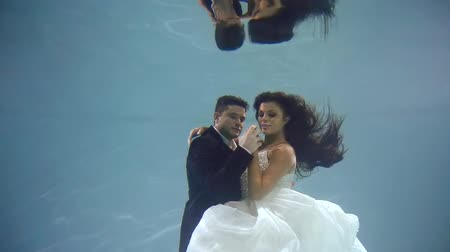 výstřední : Happy loving pair of man and woman are dressed in suits are diving in a swimming pool. Smiling and demonstrating wedding rings on hands Dostupné videozáznamy