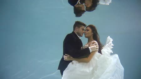 výstřední : woman dives into the water in a white dress with her man. They hold hands and look at each other. Beautiful love story.