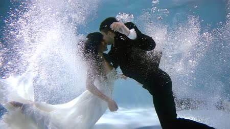 reunir : Passionate couple lovers dive simultaneously under water with splashes and bubbles. woman in wedding dress Stock Footage