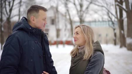 во : girl in love with white hair kisses her man on the street while walking in the Park during the day in winter Стоковые видеозаписи