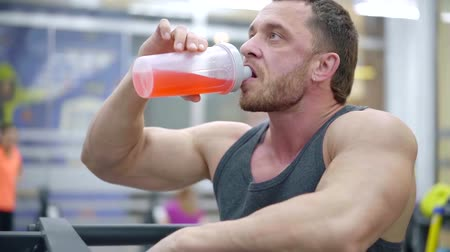 sports nutrition : portrait of an adult sports man in the gym drinking an amino acid cocktail during a workout to restore muscle mass