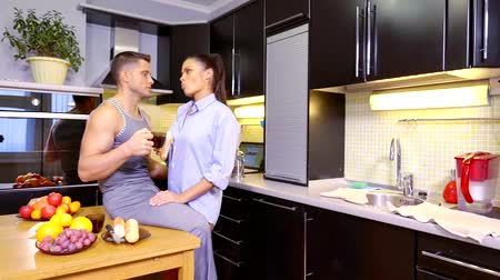 nyel : young couple in love has Breakfast in the morning at home in the kitchen with tea and a sandwich with cheese