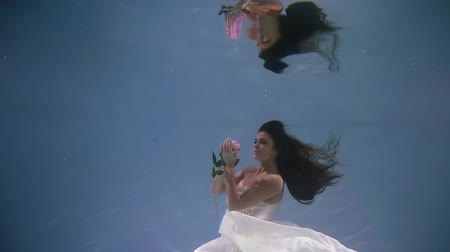 kept : mermaid bride in wedding white dress underwater with flower in hand. mirror reflection on the water surface