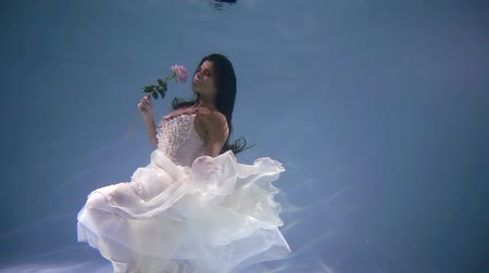 kept : cute mermaid bride in wedding big white dress with pearl floats underwater with flower in hand
