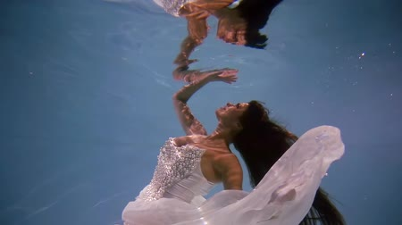 mermaid : cute mermaid bride in the wedding, big white dress with pearls swimming under water to touch the surface of the water as in a mirror