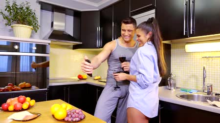 во : mistress in the kitchen of her man drinking alcohol, taking a selfie on a date at home in the kitchen with glasses of red wine Стоковые видеозаписи