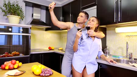 fogão : Man and woman romantic dinner in the kitchen at home. Selfie photo on mobile phone