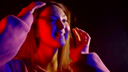 стриппер : portrait of cheerful girl with long hair in pink sweater dancing in the dark in neon light