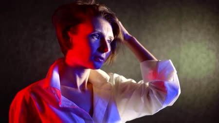 estilo : close-up portrait of a middle-aged woman in a white shirt with short hair moves in a dark room illuminated by neon light