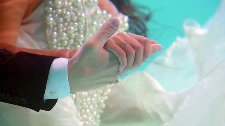flutuante : bride and groom are dressed in wedding suits and floating underwater in pool, close-up of hands Stock Footage