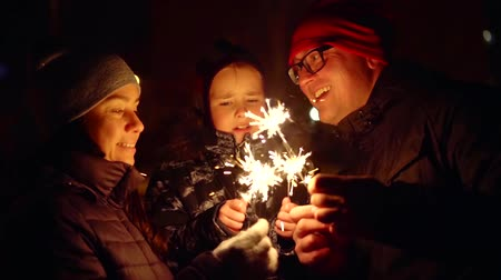 líbání : happy family is looking on burning sparklers in night street, little daughter is kissing her parents