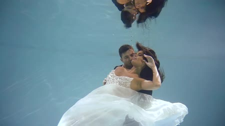 két : passionate lovers posing underwater in wedding apparels.