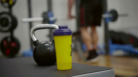 ivászat : Blurred guy working out on a background in a gym, yellow shaker and kettlebell on a bench. Stock mozgókép