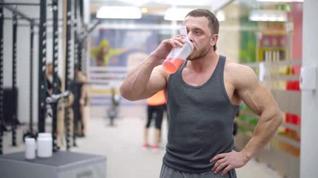 ivászat : Big ripped man resting after hard workout and drinking vitaming for muscles from shaker. Stock mozgókép
