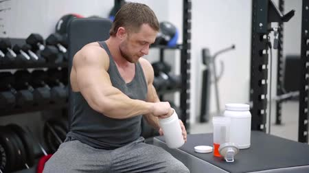 ivászat : Muscular man adding powder to the vitamin cocktail in shaker after successful heavy set, vitamins for muscles. Stock mozgókép