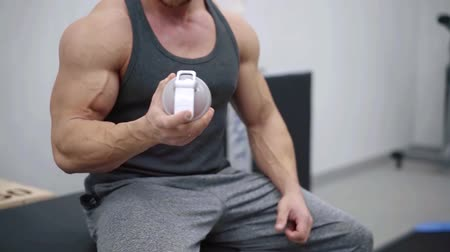 sportovci : Muscular caucasian man on diet resting after exercise And drinking protein powder from shaker in the gym Dostupné videozáznamy