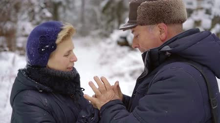 warms : older adults of retirement age walking in the winter woods. loving husband warms his woman hand