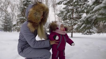 příklad : close-up of a parent walking with a child in the Park in winter. warm comfortable clothes jumpsuit. educating the generation on a real example