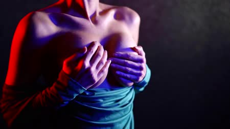 seio : slim woman is holding her naked breasts by hands and moving them up and down, close-up in dark room