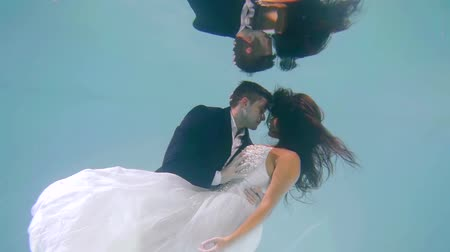 nowożeńcy : underwater shooting of kissing wedding couple, groom is holding his young pretty bride Wideo