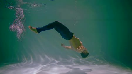 afloat : young man is lowering on floor of swimming pool underwater, floating in clear water