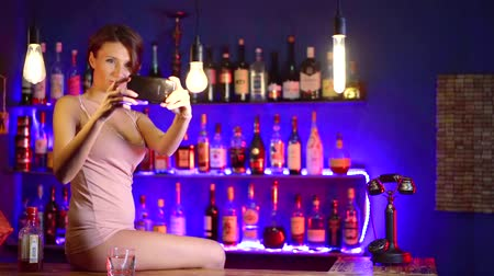výstřední : eccentric woman is sitting on a bar rack and taking selfies by smartphone, she is wearing lingerie Dostupné videozáznamy