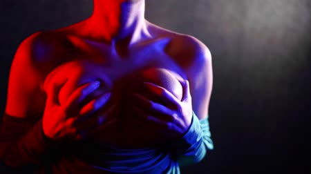 üstsüz : woman is grabbing her naked breasts by hands, standing alone in darkness, close-up view