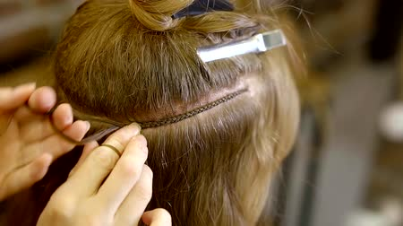 иностранец : close up. hands on hair extension weave braid a basis for additional bundles of hair