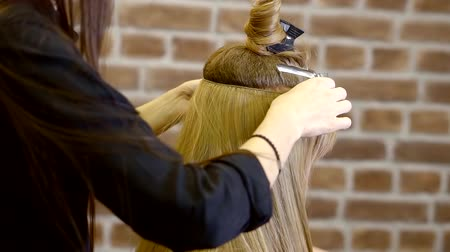 foreigner : cute blond woman of appointment in the beauty salon procedure of hair extensions by sewing the hairpiece