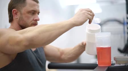 kulturystyka : Close-up of a sportsman adding powder in a shaker with red cocktail. Wideo