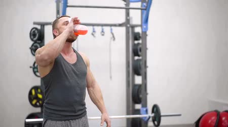 sportovci : Handsome athletic man energy cocktail from shaker in a gym, working out alone.