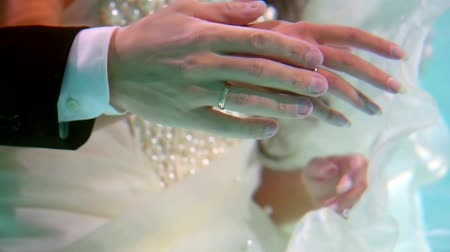 Çırpınan : Close-up shot of a mans hand with a wedding rings on his womans finger underwater, newlyweds on a shoot underwater. Stok Video