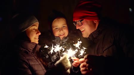 восхитительный : Outdoor portrait of a beautiful smiling family standing at night with light sparkles. Стоковые видеозаписи