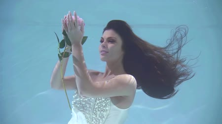 rainha : Portrait of a beautiful woman looks at a floating flower underwater, takes it and smells.