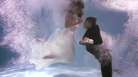 jumped : Two lovers jumped in a pool and slowly going down underwater in wedding dresses